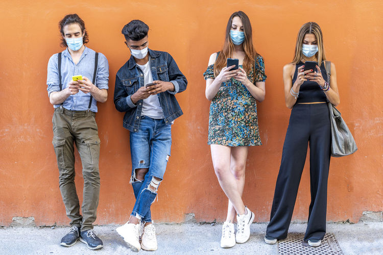 Full length of friend wearing flu mask standing by orange wall outdoors
