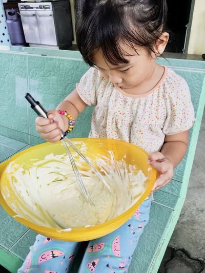High angle view of girl mixing food in bowl at home