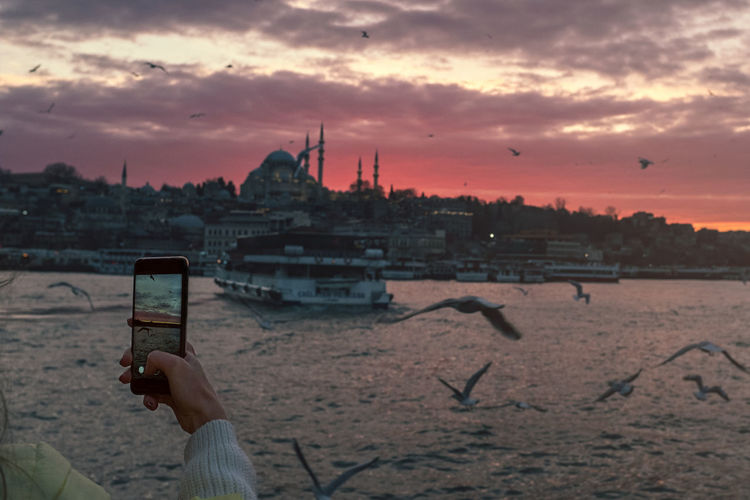 Sky Sunset Cloud - Sky One Person Architecture Technology Human Hand Built Structure Building Exterior Holding Photography Themes Real People Wireless Technology Smart Phone Connection Hand Portable Information Device City Nature Photographing Outdoors Cityscape Golden Horn Karaköy Galata Bridge