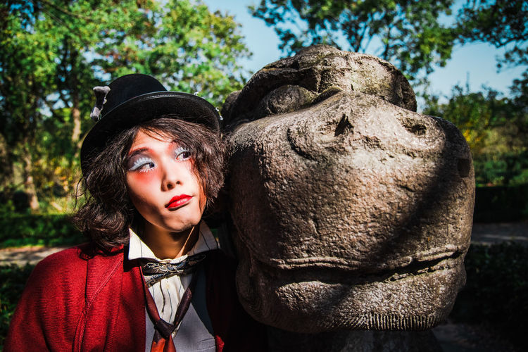 Portrait of young man cosplaying mad hatter with statue against trees