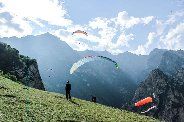 People on mountain range against sky