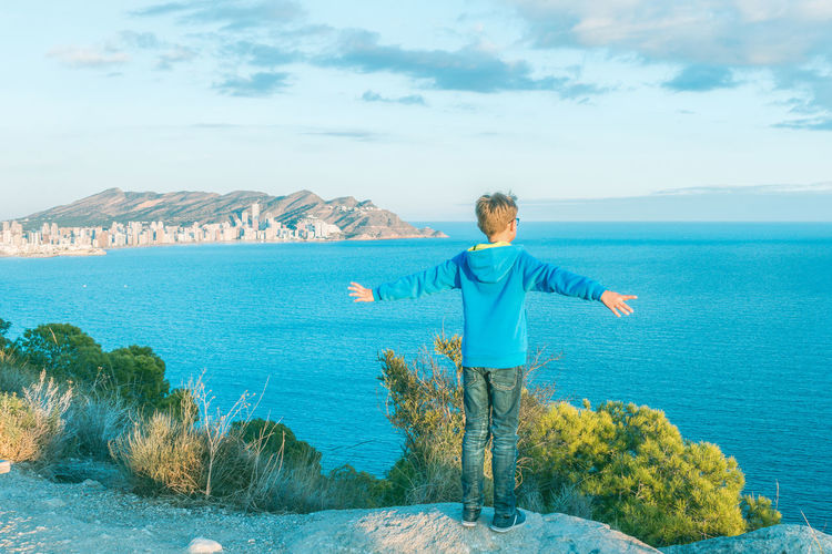 Rear View Of Boy Standing With Arms Outstretched While Looking At Sea Against Sky