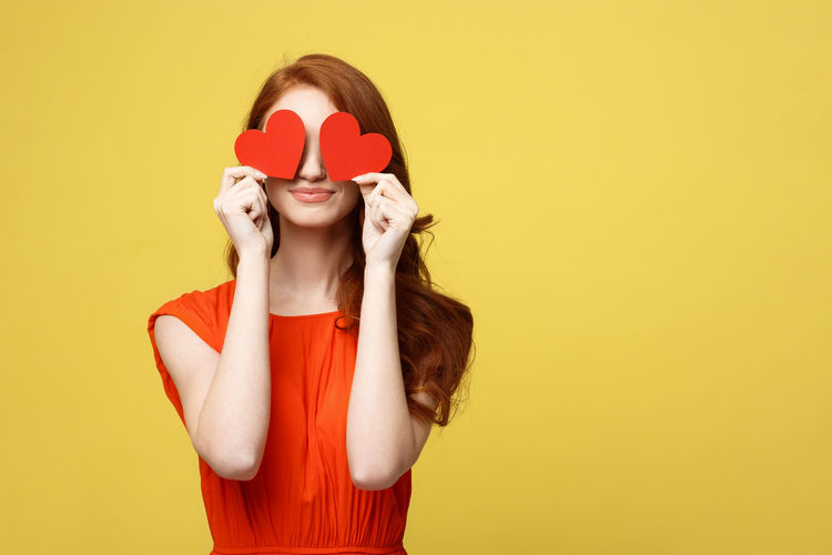 Young woman holding red heart shape paper while standing against yellow background