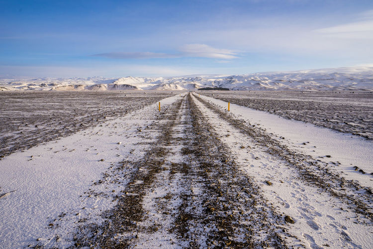 Road amidst snowcapped landscape against sky during winter