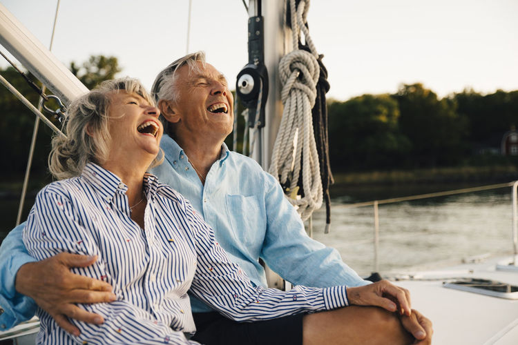 Rear view of couple sitting on boat