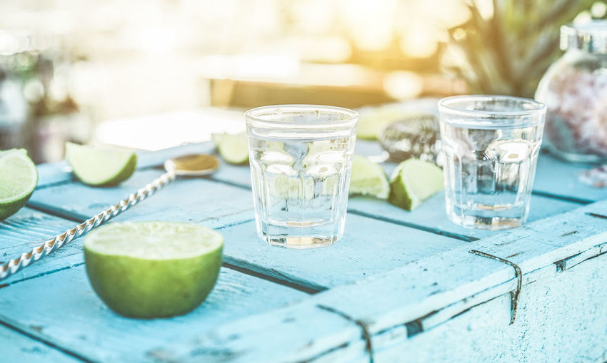 Close-up of limes and drink on table