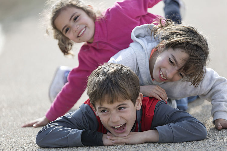 Three children lying on the floor one on top of the other. Horizontal shot with natural light Children Children's Portraits Spanish Tree Children Caucasian Ethnicity Child Childhood Day Family Leisure Activity Looking At Camera Looking At The Camera Love Outdoors People person Portrait Smiling Togetherness Toothy Smile