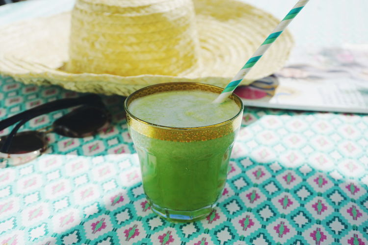 enjoying the summer with reading and drinking a celery drink Green Summer Drink Healthy Summer Summertime Celery Smoothie Drink Drinking Glass Fruit Drinking Straw Matcha Tea Close-up Food And Drink Green Color Frothy Drink Froth Detox