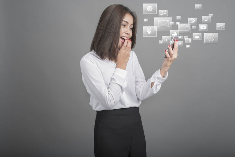 Digital composite image of cheerful businesswoman using mobile phone against gray background