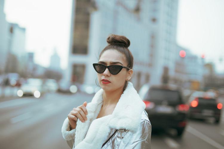 Portrait of woman in sunglasses against buildings