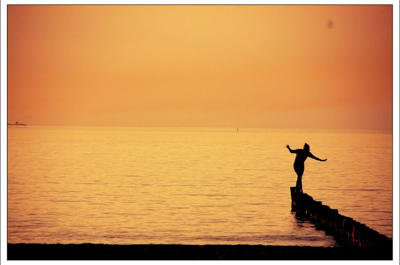 Silhouette person balancing on pier amidst sea against clear sky