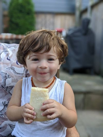 Portrait of boy holding a big wedge of cheese