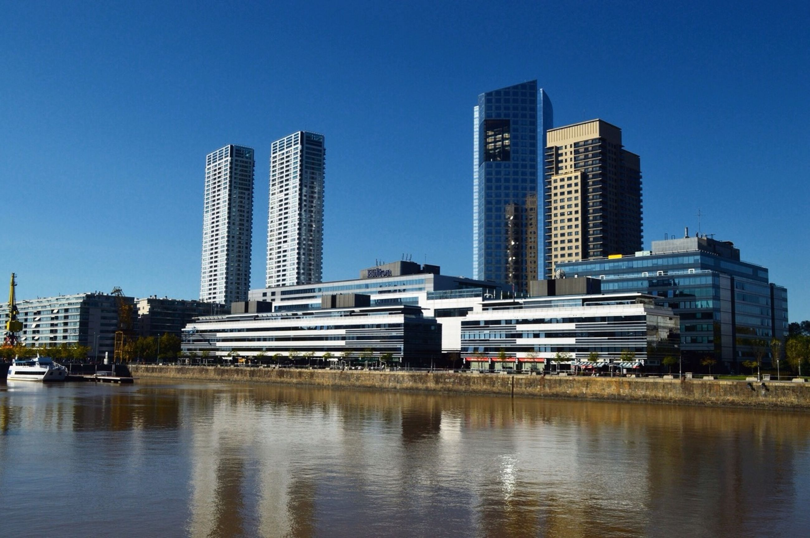 building exterior, architecture, city, skyscraper, built structure, water, modern, office building, clear sky, urban skyline, waterfront, tall - high, cityscape, tower, blue, river, reflection, financial district, building, skyline