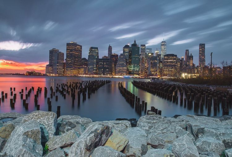 Groynes in east river against illuminated skyscrapers at manhattan