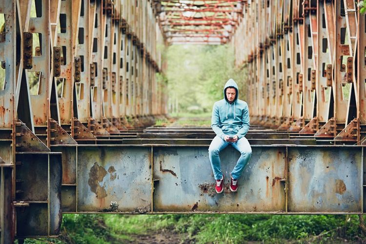Full length of young man using phone while sitting on abandoned bridge