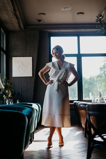 Young woman standing on table in restaurant