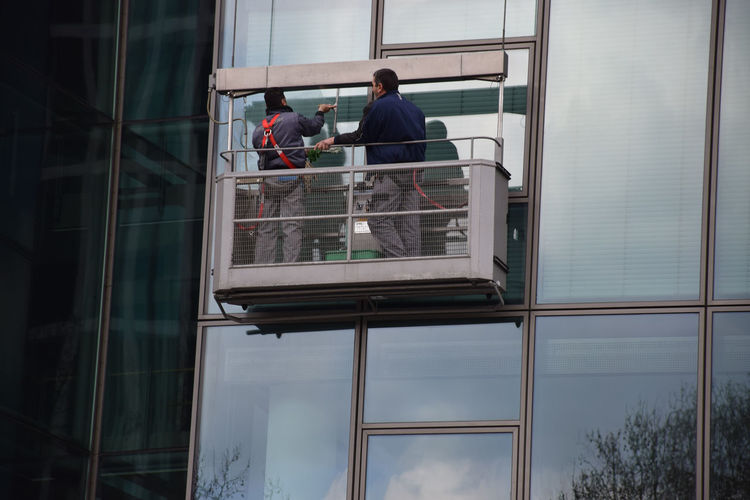 Low angle view of window washers cleaning glass building