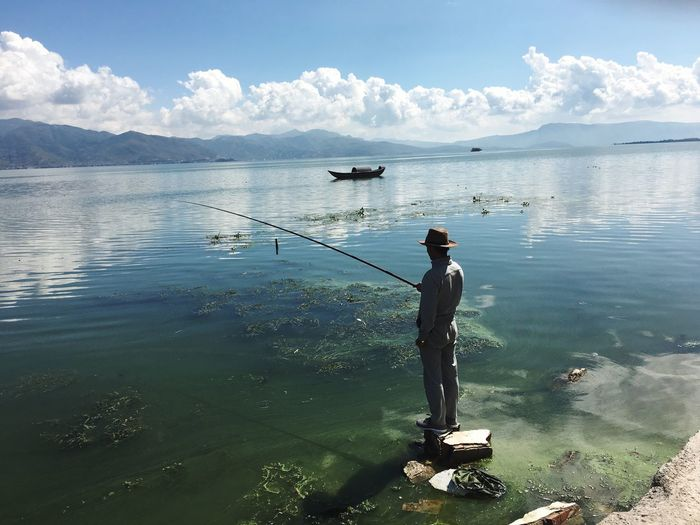 Erhai Lake,Dali Water Nature Full Length Sky Beauty In Nature Occupation Standing Sea Day Fishing One Person Outdoors Tranquility Fisherman Cap Mountain Working Live For The Story China Beauty China Photos China China Style Breathing Space Breathing Space Lost In The Landscape