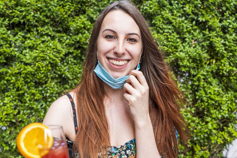 Portrait of smiling young with flu mask holding drink