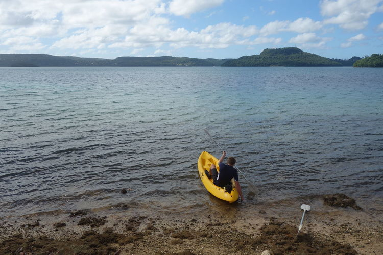 Rear View Of Man Kayaking In Sea Against Sky