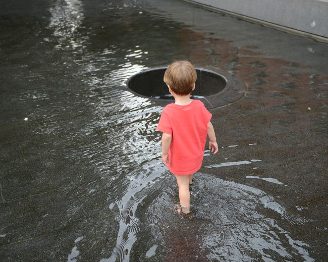 Rear View Of Boy Standing In Water