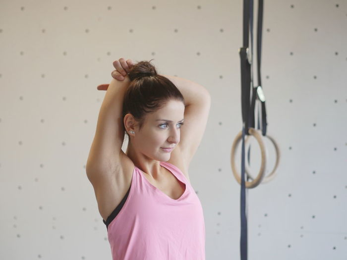 Young Woman Exercising By Gymnastic Rings