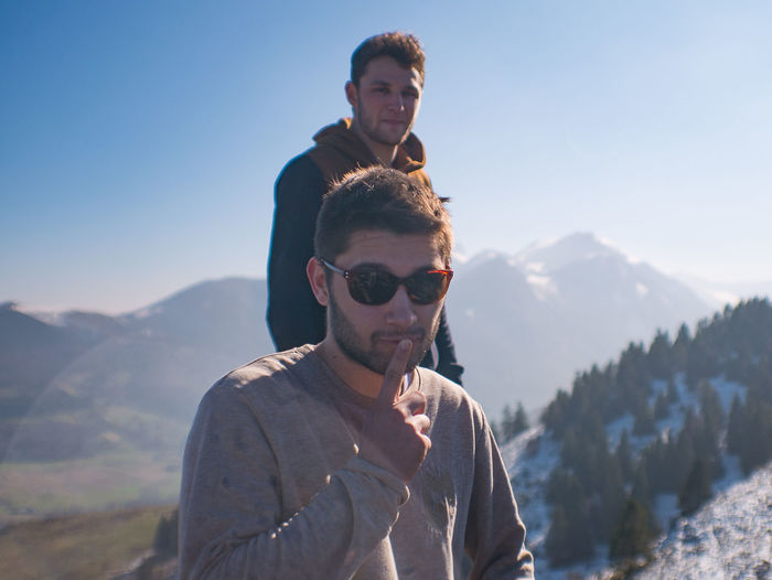 Portrait of friends on mountain against sky