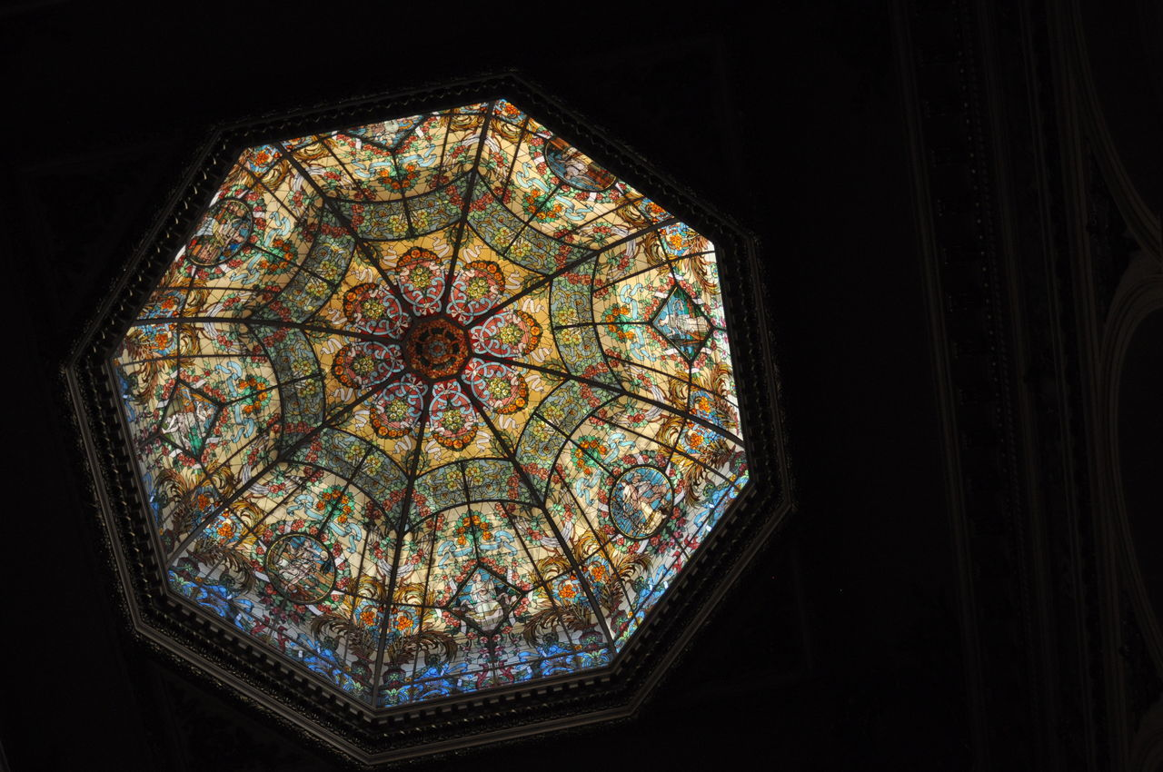 indoors, stained glass, window, glass, low angle view, no people, place of worship, architecture, glass - material, religion, design, built structure, belief, building, pattern, spirituality, multi colored, shape, dark, ceiling, ornate, directly below, floral pattern