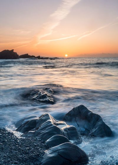Aquatic Sport Beach Beauty In Nature Cloud - Sky Flowing Water Horizon Over Water Idyllic Land Motion Nature No People Orange Color Outdoors Power In Nature Rock Scenics - Nature Sea Sky Sport Sunset Water Wave