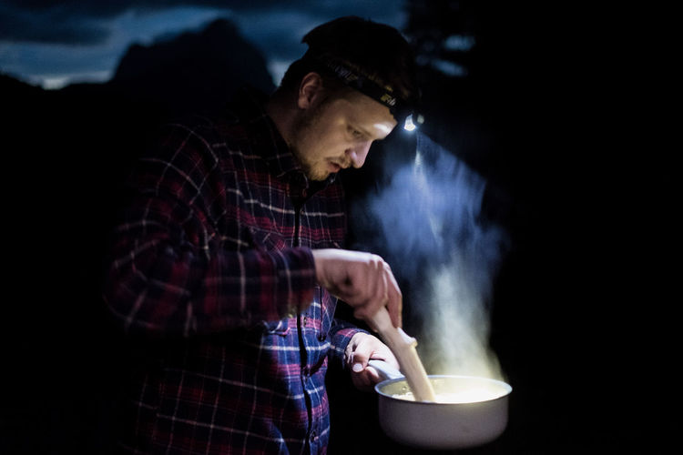 Young man preparing food using headlamp in forest at night