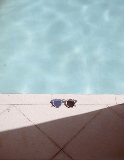 High angle view of sunglasses on poolside