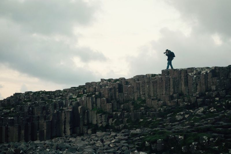 Low angle view of man photographing on rock formations