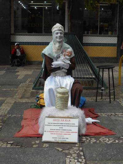 "Susan´s Series: Street Vendors in Downtown São Paulo (often referred to as a ""Micro-Empresa"", or Micro-Business) . ""Arte na Rua"" - ""Art in the Street"" or ""Street Art"" by Sr. Fausto Santos Lima. A Human Statue street art representation in downtown São Paulo near Rua XV de Novembro. He provided permission to take his photo -- in the event the photo ever gets licensed I will be splitting the proceeds with Mr. Lima. He is a regular at this spot in downtown São Paulo, persistently plying his street art trade day in and day out. City Life Small Business Heroes Street Vendor Susan A. Case Sabir Unretouched Photography Art And Craft Arte Na Rua Creativity Downtown São Paulo Human Representation Human Statue Micro-business Microempresa Outdoors Real People Representation Selling On The Street Sidewalk Sitting Statue Street Art Street Photography Text Urban Photography"