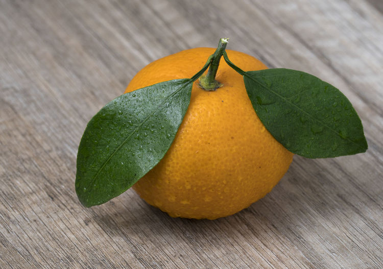 Fresh ripe tangerine with leaves on a wooden background. Close up view. Orange; Fruit; Citrus; Fresh; Sweet; Food; Healthy; Tangerine; Mandarin; Ripe; Background; Juicy; Group; Tropical; Diet; Organic; Vegetarian; Closeup; Yellow; Natural; Clementine; Nature; Tasty; Color; Delicious; Green; Vitamin; Wooden; Eating; Snack; Lea Leaf Plant Part Table Wood - Material Fruit Food And Drink Healthy Eating Food Freshness Green Color Close-up Citrus Fruit Orange Color No People Wellbeing Still Life Yellow Nature Focus On Foreground Orange Leaves