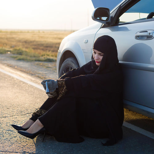 Woman wearing hijab sitting by damaged car on road