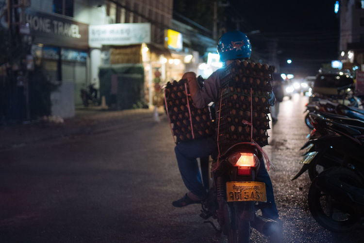 City Transportation Mode Of Transportation Night Street Land Vehicle Motorcycle Illuminated Real People Architecture Building Exterior Incidental People Built Structure Road Men People City Life Helmet Rear View Riding Outdoors Egg Egg Delivery Laos