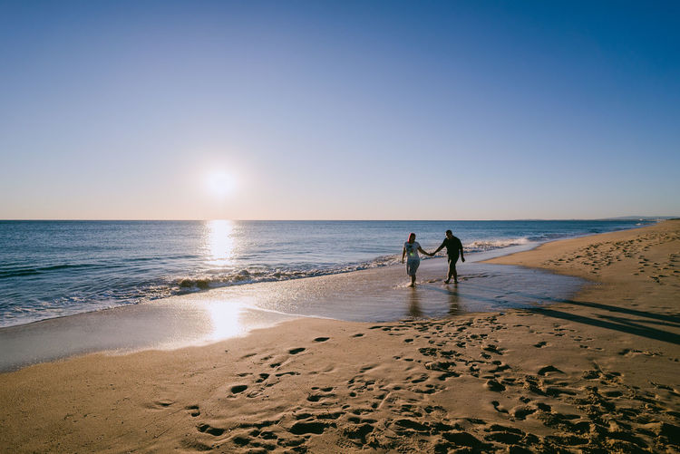 Couple Walking At Beach Against Clear Sky During Sunset