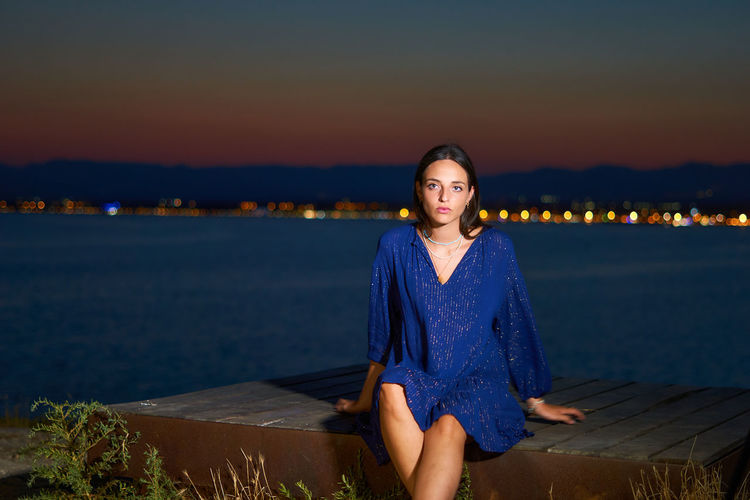 Portrait of young woman sitting against blue sky during sunset
