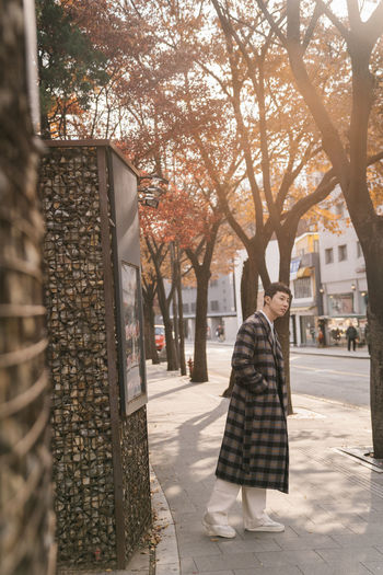 Woman standing by tree on street in city