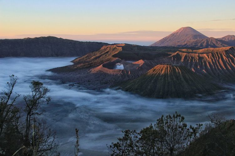 Panoramic view of arid landscape against sky during sunset. mount bromo national park