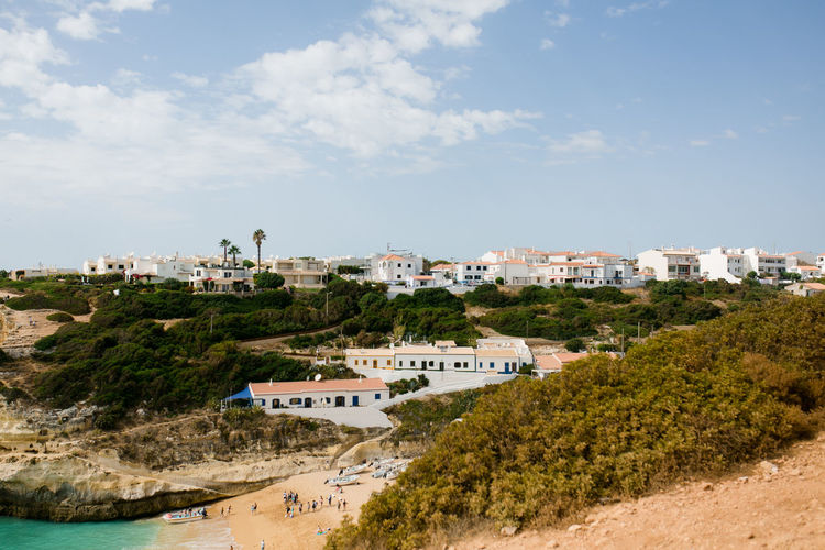 Scenic view of beach by buildings against sky