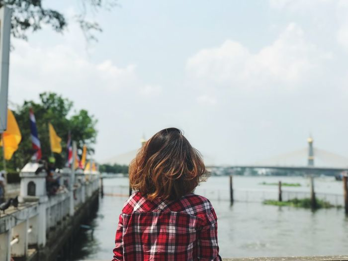 Rear view of woman standing at riverbank