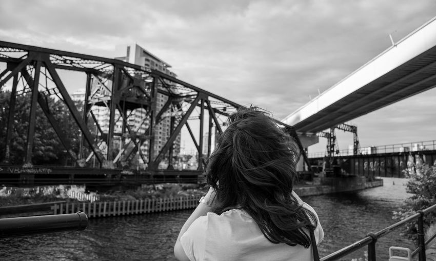 Rear view of woman on bridge over river against sky