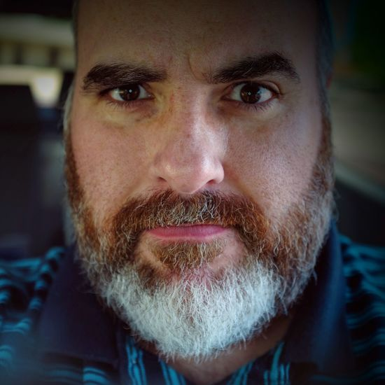Close-Up Portrait Of Serious Man With Beard In Car