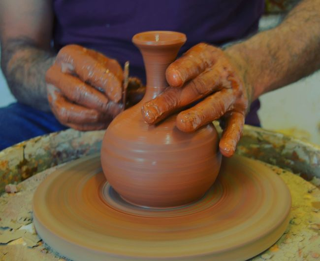 Midsection of man working in mud pottery