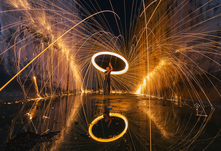 Man spinning wire wool while standing on street at night