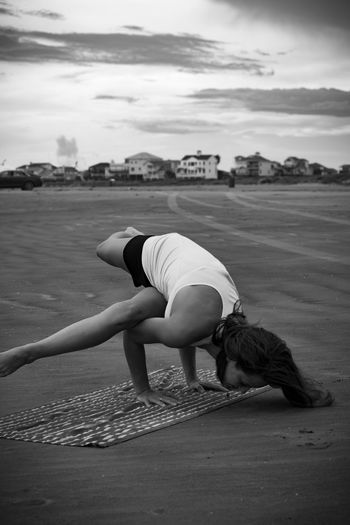 Full length of woman practicing handstand at beach