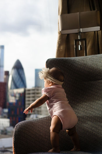 Rear view of baby girl standing on a chair