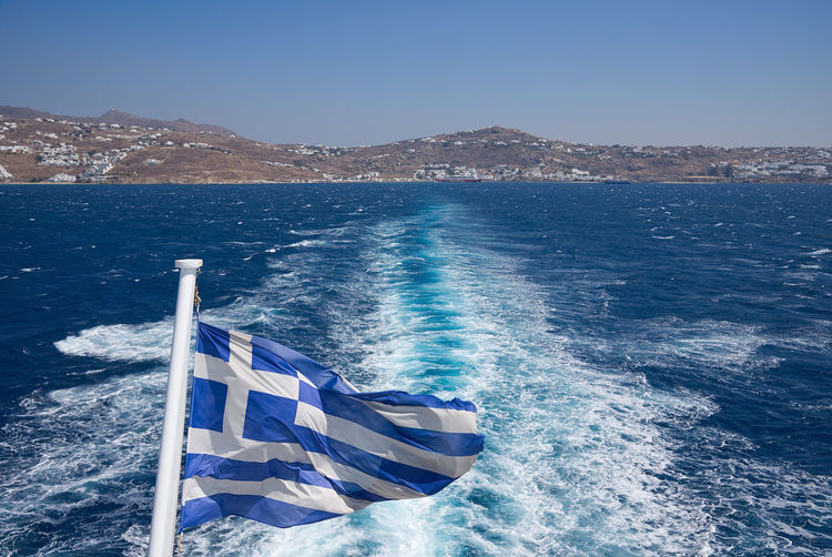 Greek flag against sea on sunny day