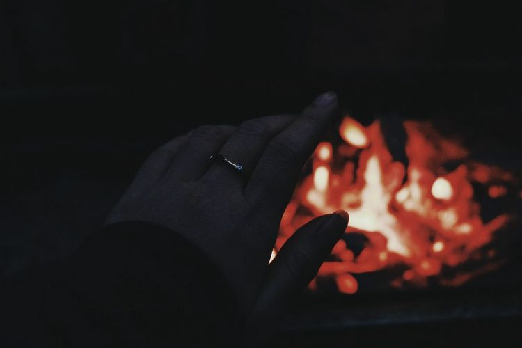 Close-up of hands burning in the dark
